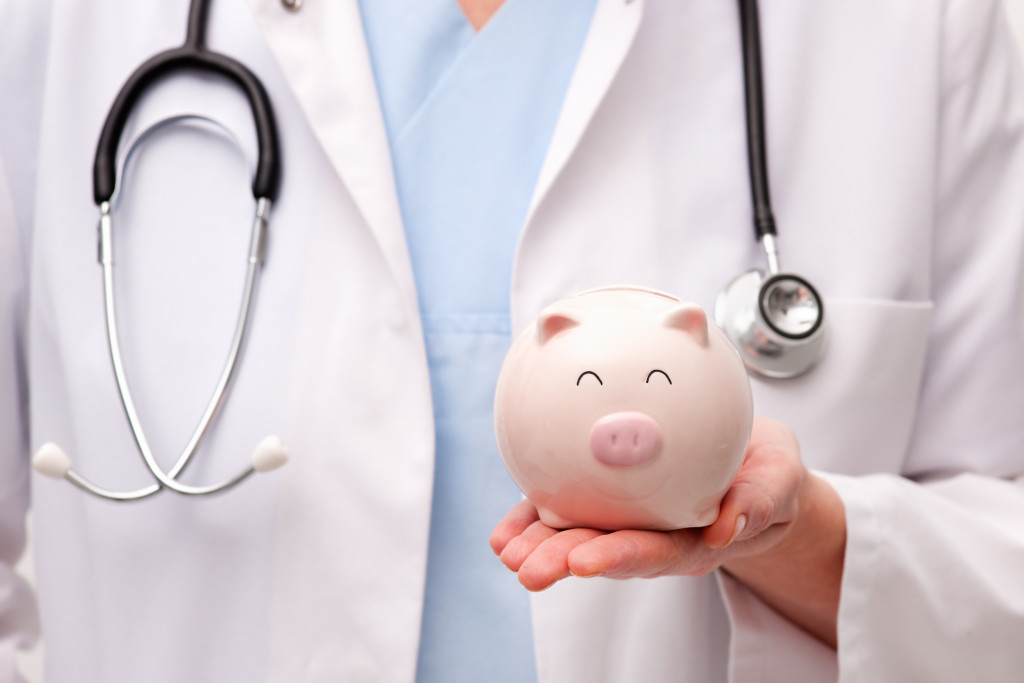 Female doctor with stethoscope holding piggy bank