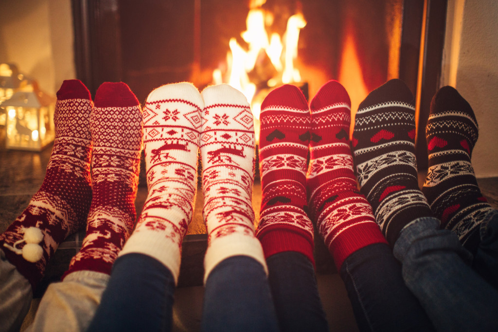 Feet in Christmas socks near fireplace.  Four pair of feet warming up. Friends at cozy winter vacation.