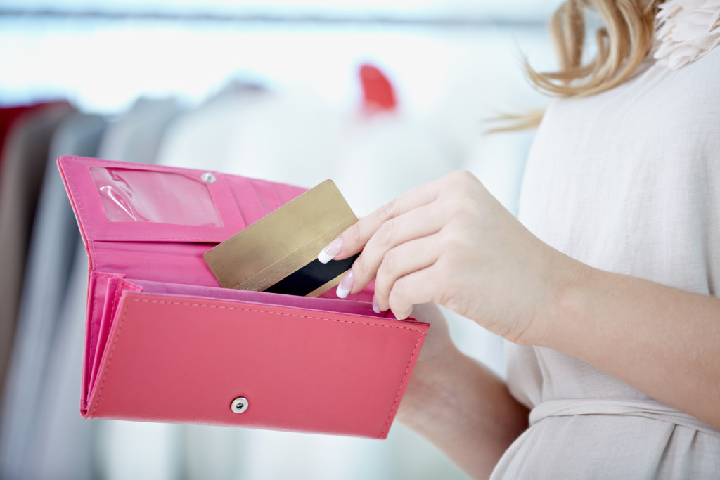 Woman taking her credit card out of wallet