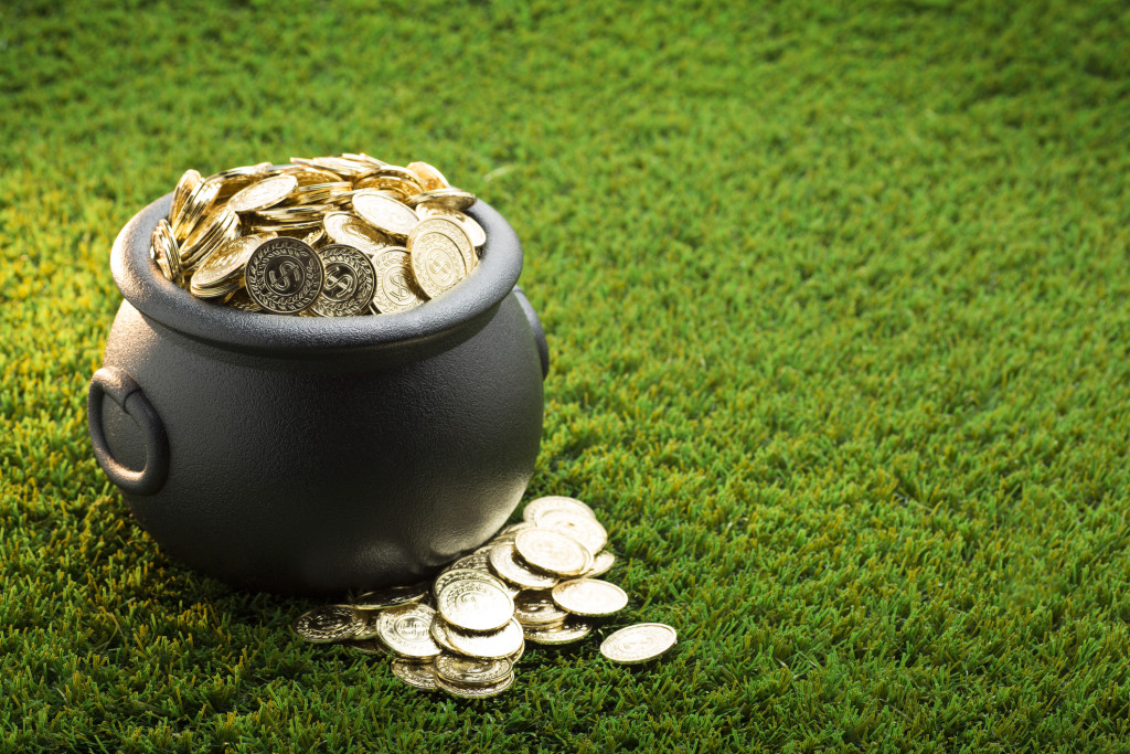 This is a close up photo of a large black pot of gold on the grass symbolizing St. Patrick's Day.
