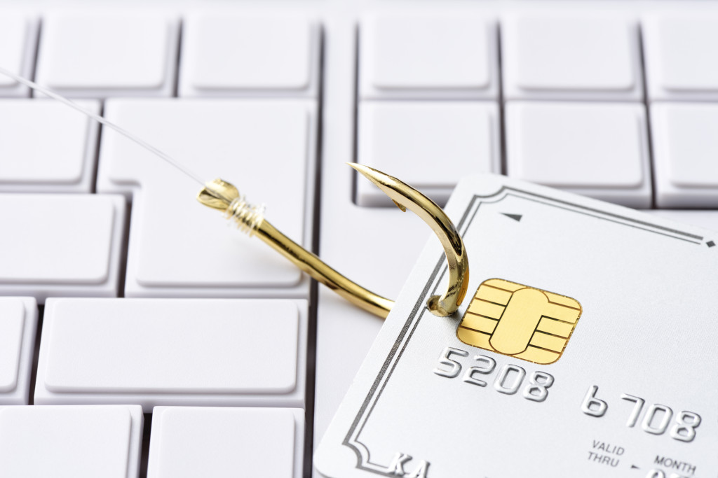 Close-up of credit card and gold fishing hook on blank computer keyboard, with shallow depth of field.