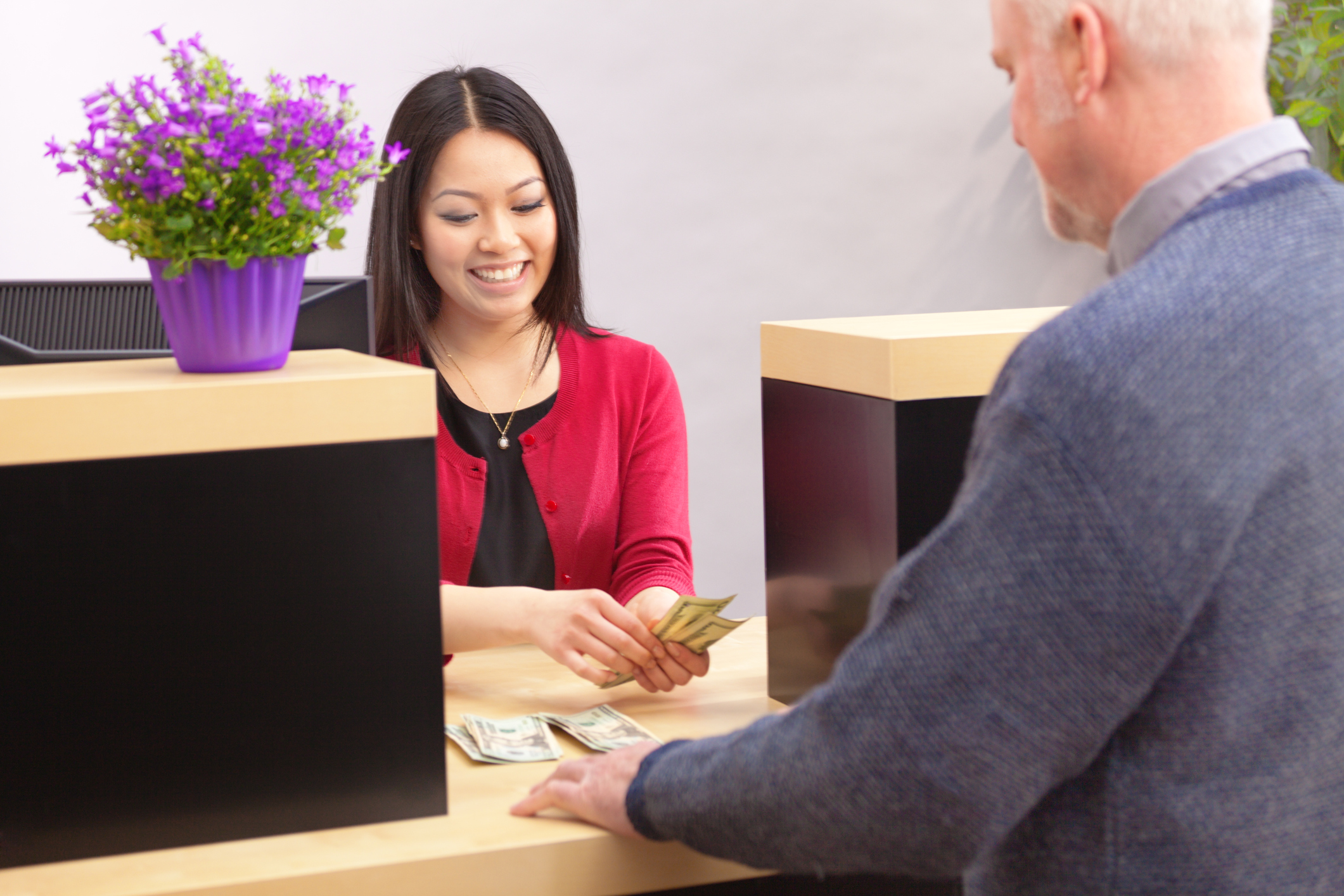 An adult man bank customer making a financial transaction with a bank teller over the counter in a retail bank. The woman Asian bank teller is smiling and cheerfully providing the customer service. Photographed behind the shoulder of the customer in a horizontal format.